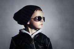 Moderner Kinderjunge in der Sonnenbrille Kind in der schwarzen Kappe Herbstart Winter Little Boy stockfotos