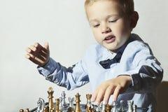 Moderner kleiner Junge, der Schach spielt Intelligentes Kind Fashion Children Lizenzfreie Stockfotografie