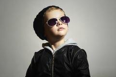 Moderner kleiner Junge in der Sonnenbrille Kind Aufstellung wenigen Modells in der schwarzen Kappe Stockfotografie