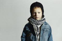 Moderner kleiner Junge im Schal und in den Jeans Getrennt auf weißem Hintergrund lizenzfreie stockfotografie
