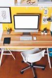 Moderner kreativer Arbeitsplatz auf gelber Wand Lizenzfreie Stockfotos