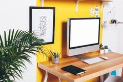 Moderner kreativer Arbeitsplatz auf gelber Wand Stockbild