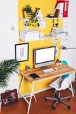Moderner kreativer Arbeitsplatz auf gelber Wand Stockfotografie