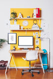 Moderner kreativer Arbeitsplatz auf gelber Wand Stockbilder