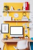 Moderner kreativer Arbeitsplatz auf gelber Wand Lizenzfreie Stockfotografie