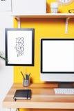 Moderner kreativer Arbeitsplatz auf gelber Wand Stockfoto