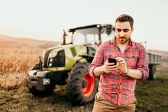 Moderner Landwirt, der unter Verwendung des Smartphone in der modernen Landwirtschaft mit Traktorhintergrund arbeitet und erntet stockbilder