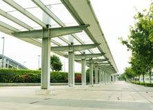 Moderner langer Regenkorridor entlang Pflasterung oder Bürgersteig auf der Seite der Stadtstraße stockbild