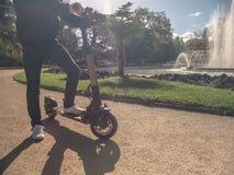 Moderner Mann auf elektrischem Roller in Sunny Park mit Brunnen 1 stockbilder