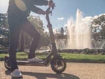 Moderner Mann auf elektrischem Roller in Sunny Park mit Brunnen 3 lizenzfreie stockfotos