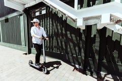 Moderner Mann kleidete weißes Hemd und schwarzen die Hosen, die an der Straße mit elektrischem Roller stehen stockfotos