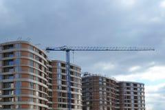 Moderner mehrstöckiger komplexer im Bau und Bauwohnkran gegen den grauen Herbsthimmel stockbilder