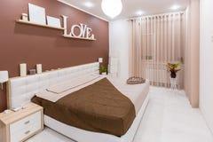 Moderner Minimalismusart-Schlafzimmerinnenraum in den hellen warmen Tönen lizenzfreie stockfotos