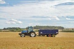 Moderner neuer Holland-Traktor, der blauen Anhänger zieht Lizenzfreie Stockbilder