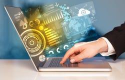 Moderner Notebook mit zukünftigen Technologiesymbolen Stockfotografie