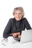 Moderner Pensionär, der einen Laptop verwendet Stockfotografie