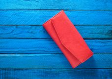 Moderner roter Geldbeutel auf einem blauen hölzernen Hintergrund Beschneidungspfad eingeschlossen Tendenz des Minimalismus Stockfotografie