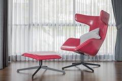 Moderner roter Stuhl auf Bretterboden mit Vorhang Lizenzfreies Stockfoto