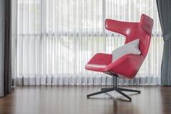Moderner roter Stuhl auf Bretterboden mit Vorhang Lizenzfreie Stockfotos