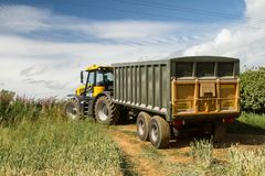 Moderner schneller Traktor trac JCB, der grünen gelben Anhänger zieht Lizenzfreie Stockfotos