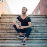 Moderner stilvoller blonder Mann des Hippies, der in der Treppe sitzt Stockbild