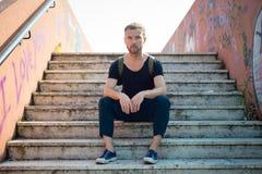 Moderner stilvoller blonder Mann des Hippies, der in der Treppe sitzt Lizenzfreie Stockfotografie
