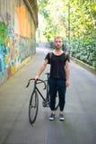 Moderner stilvoller blonder Mann des Hippies mit Fahrrad Stockbild