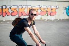 Moderner stilvoller blonder Mann des Hippies mit Fahrrad Stockfotos
