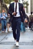 Moderner stilvoller Geschäftsmann, der auf Stadtstraße geht und am Handy simst Stockfotos