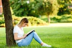 Moderner Student, der im Park unter dem Baum sitzt und das BO liest Lizenzfreies Stockfoto