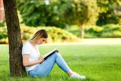 Moderner Student, der im Park unter dem Baum sitzt und das BO liest Stockbild