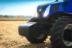 Moderner Traktor, der in einer Feldnahaufnahme arbeitet Lizenzfreie Stockfotos