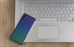 Moderner und Entwurfsnotebook oder Laptop und Smartphone, beweglich mit dreifacher Kamera in einer hellen hölzernen Tabelle stockbilder