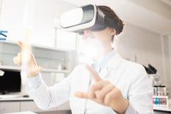 Moderner Wissenschaftler, der über Gene mit VR-Simulator lernt lizenzfreie stockfotos