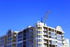 Moderner Wolkenkratzer mit dem Hochziehen des Kranes Lizenzfreie Stockfotos