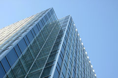 Modernes Bürohaus, das den blauen Himmel reflektiert stockfotos