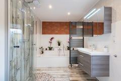Modernes Badezimmer in der Weinleseart mit Wanne, Badewanne, Glasdusche und schwarzem Tuchtrockner stockfotos