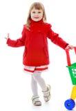 Modernes blondes kleines Mädchen mit einem Warenkorb in Stockfoto