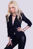 Modernes blondes Mädchen, das auf grauem Hintergrund aufwirft Stockfoto