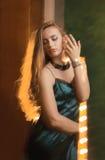 Modernes blondes Modell im Kleid, das auf einem Hintergrund von lig aufwirft Lizenzfreie Stockfotografie