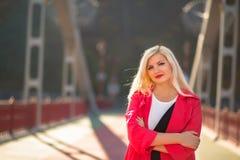 Modernes blondes Modell mit dem hellen Make-up, das in rotem Mantel a aufwirft Stockbild