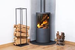 Modernes brennendes Ofenholz zeichnet Gestell auf Stockfotografie