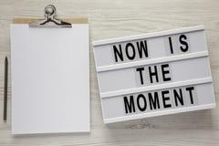 Modernes Brett mit Text 'ist jetzt der Moment ', Klemmbrett mit Leerbeleg auf einem weißen Holztisch, Draufsicht Von oben flache  stockbild