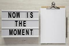 Modernes Brett mit Text 'ist jetzt der Moment ', Klemmbrett mit Leerbeleg auf einer weißen Holzoberfläche, Draufsicht Von oben fl lizenzfreies stockbild