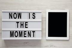 Modernes Brett mit Text 'ist jetzt der Moment ', Tablette mit leerem Bildschirm auf einem weißen hölzernen Hintergrund, obenliege lizenzfreies stockbild