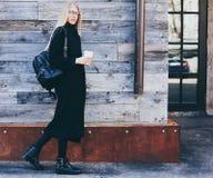 Modernes Café, schönes Äußeres schöne junge blonde Frau in einem schwarzen Kleid, welches das Stillstehen, einen Kaffee genießend Lizenzfreie Stockfotos