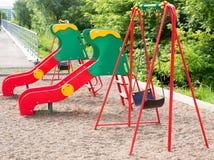 Modernes der Spielplatz-Dia und Schwingen des Kindes stockfoto