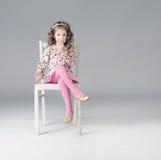 Süßes durchdachtes kleines Mädchen, das auf dem weißen Stuhl, viel O sitzt Lizenzfreie Stockfotografie