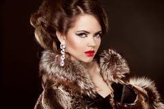Modernes elegantes Mädchen im Luxuspelz-Mantel. Rote Lippen. Frisur Lizenzfreie Stockbilder