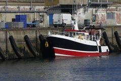 Modernes Fischerboot koppelte im Hafen von Lorient, Frankreich mit Lager im Hintergrund an Stockfotos